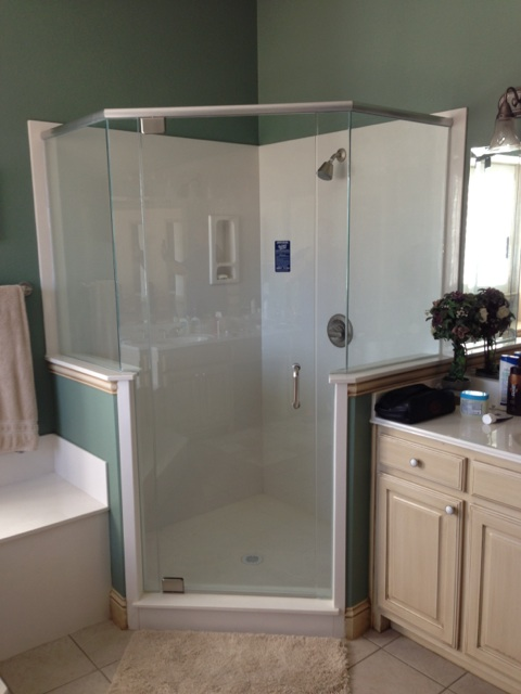 Frameless shower enclosure with header door with 4 panels mitered